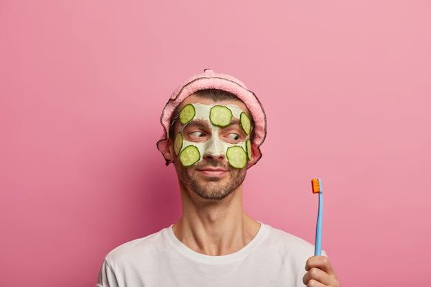 Bell'uomo applica maschera di argilla e cetrioli freschi, guarda lo spazzolino da denti, ha procedure mattutine a casa