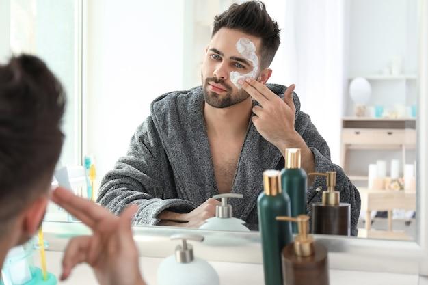 Красивый мужчина, наносящий маску из глины на лицо дома