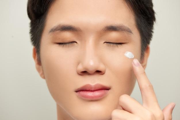 Красивый мужчина, применяя крем для глаз