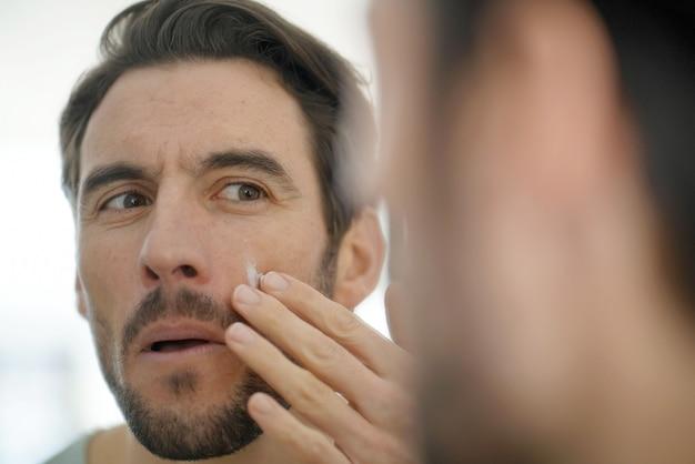 Handsome man applying face cream looking in mirror