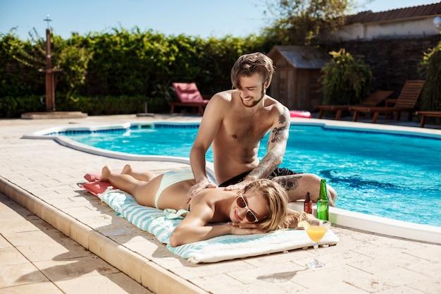 スイミングプールのそばの女性に日焼け止めクリームを適用するハンサムな男