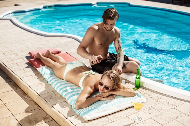 Handsome man applying suntan cream on woman near swimming pool