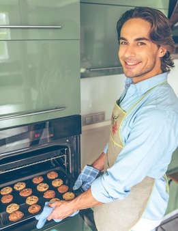 Handsome man in apron is looking at camera and smiling.
