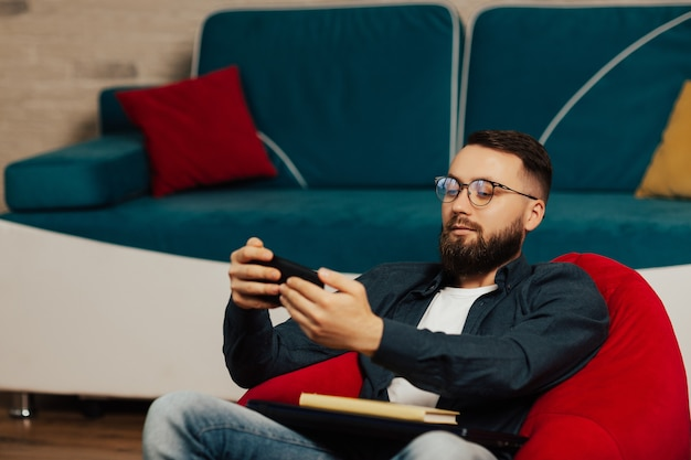 집에서 안락의 자에 앉아있는 동안 잘 생긴 남자가 스마트 폰 장치를 사용하고 있습니다.