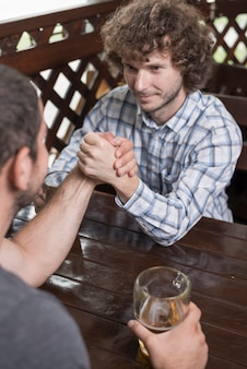 Handsome man arm wrestling with friend in pub