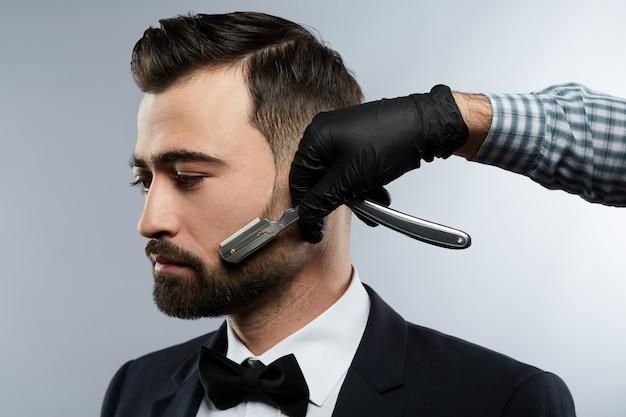 Blak 양복과 넥타이, 스튜디오 배경, 이발소 개념에서 검은 머리를 가진 남자를위한 수염 형태를 만드는 셔츠를 입고 남자의 손을 입고 이발소에서 잘 생긴 남자.