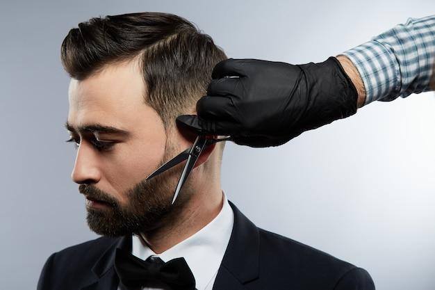 Blak 양복과 넥타이, 스튜디오 배경에서 검은 머리를 가진 남자를위한 수염 형태를 만드는 셔츠를 입고 남자의 손을 입고 이발소에서 잘 생긴 남자, 초상화.