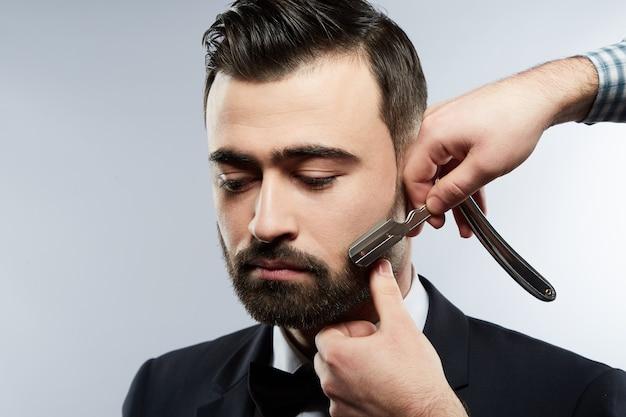 Blak 양복과 넥타이, 스튜디오 배경에서 검은 머리를 가진 남자를위한 수염 양식을 만드는 셔츠를 입고 남자의 손을 입고 이발소에서 잘 생긴 남자.