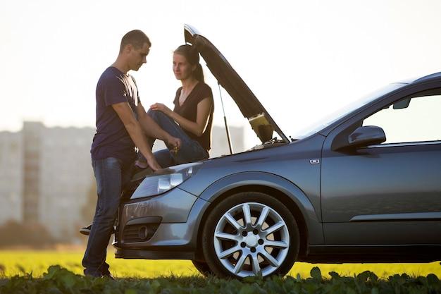 딥 스틱과 맑은 하늘 배경에서 보는 매력적인 여자를 사용하여 엔진의 오일 수준을 확인 팝 후드와 함께 차에서 잘 생긴 남자. 운송, 차량 문제 및 고장 개념.