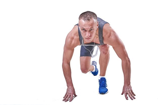 Красивый мужчина на старте в спортивной одежде, изолированные на белом фоне