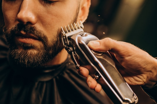Handsome man at barbershop shaving beard