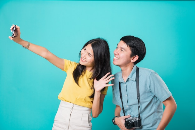 Handsome man, beautiful woman couple smile standing wear shirt, taking selfie photo on a smartphone