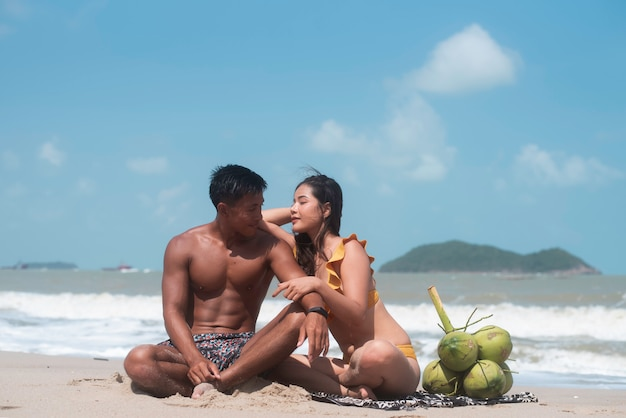 Handsome man and beautiful woman wearing swimming suit,sittting on the beach,with romantic feeling,model posing