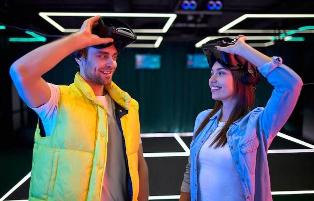 Handsome man and beautiful young woman with glasses of virtual reality. vr, games, entertainment, future technology concept. couple with virtual reality headset having fun together.