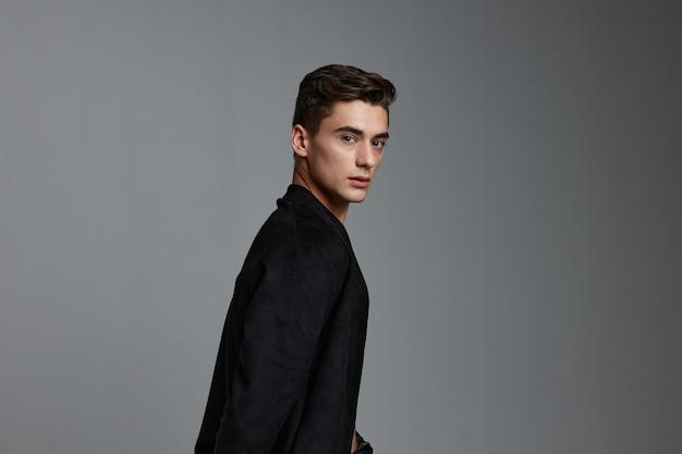Красивый мужчина черный пиджак привлекательный вид моды прическа.