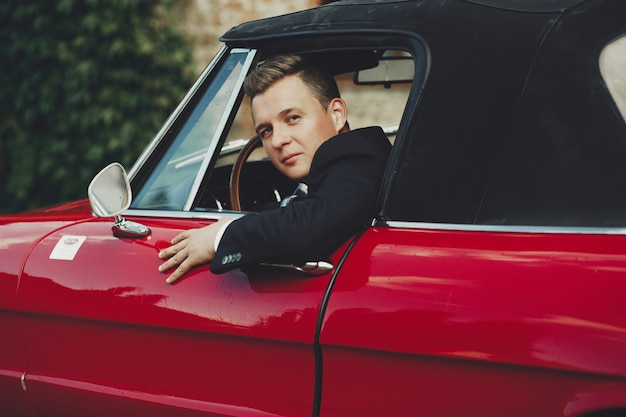 Handsome man in black suit sits in a red retro italian car