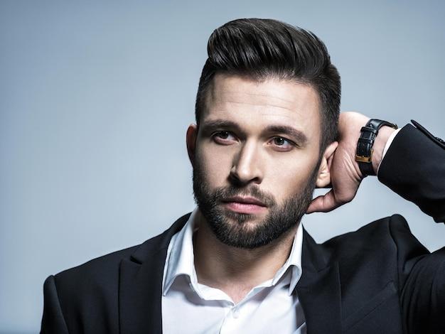 Bell'uomo in abito nero con camicia bianca - in posa ragazzo attraente con l'acconciatura di moda. uomo fiducioso con barba corta. ragazzo adulto con capelli castani.