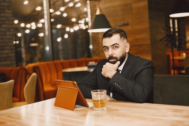 Bell'uomo in abito nero, lavora in un caffè