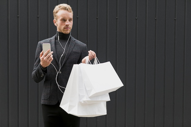 Handsome man in black with earphones and smartphone
