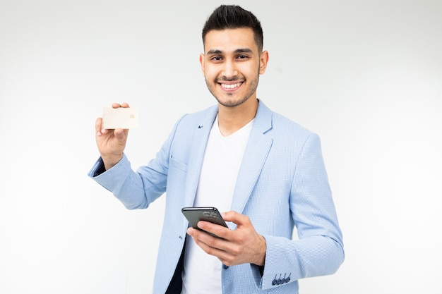 Handsome man in a blue jacket with a credit card with a mockup and a phone in his hand on a white studio background