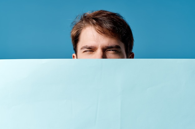 青い背景を宣伝するハンサムな男の青いシートプレゼンテーション