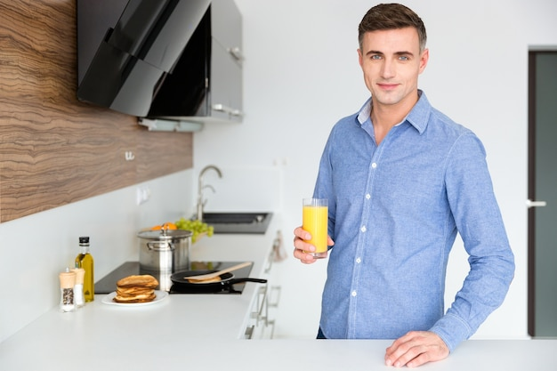 Handsome man in blue shirt standing on the kitchen and drinking orange juice
