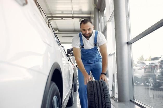 L'uomo bello in un'uniforme blu controlla l'automobile