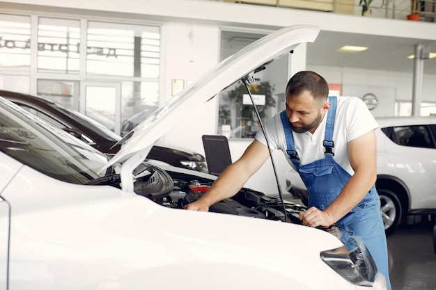 Handsome man in a blue uniform checks the car