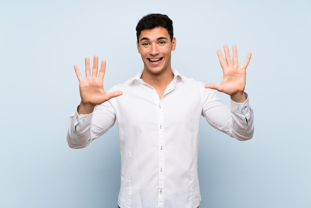 Handsome man over blue wall counting ten with fingers