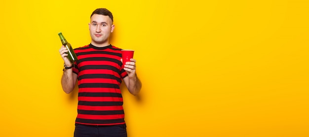 Handsome man in bright t-shirt with beer