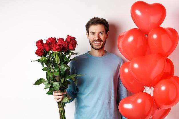 잘생긴 남자는 발렌타인 데이 날짜에 꽃과 빨간 하트 풍선을 가져옵니다. 장미 꽃다발과 연인을 위한 선물을 든 낭만적인 남자친구는 흰색 배경 위에 서 있습니다.