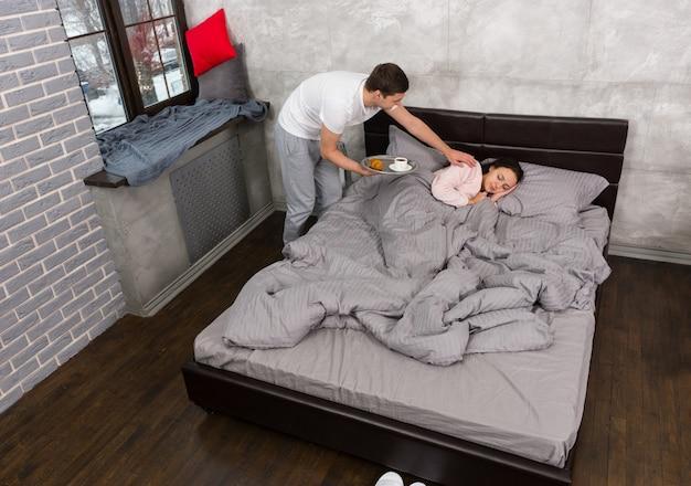 Красивый мужчина принес жене завтрак в постели, пока она спала в постели в пижаме в спальне в стиле лофт