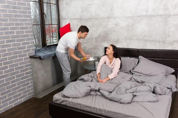 Красивый мужчина принес завтрак в постель, а его девушка проснулась и сидит в постели в пижаме в спальне в стиле лофт