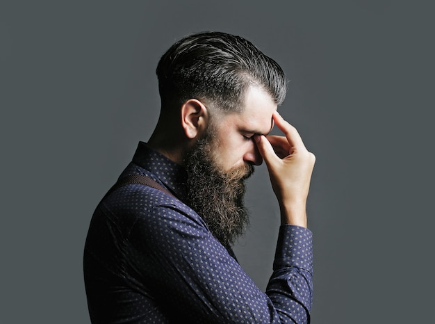 Handsome man businessman or hipster with long beard and moustache thinks with closed eyes on gray