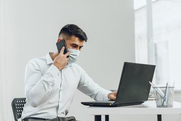 실내에서 자신의 휴대 전화에 얘기하는 동안 자신의 노트북을 사용하는 의료 마스크에 잘 생긴 남자 사업가