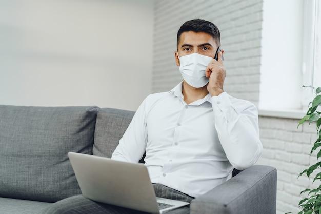 그의 핸드폰에 얘기하는 동안 자신의 노트북을 사용하는 의료 마스크에 잘 생긴 남자 사업가