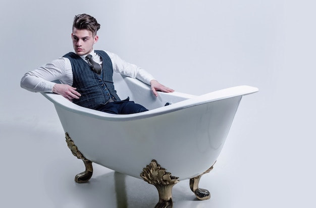 Handsome man or businessman with stylish haircut, hair, in fashion business wear, vest, tie, shirt and pants relaxing in classic bath, white tub, on grey background