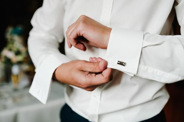 Красивый мужчина застегивает запонки на белой рубашке. элегантные мужские золотые запонки жениха. подготовка к свадьбе утро жениха.