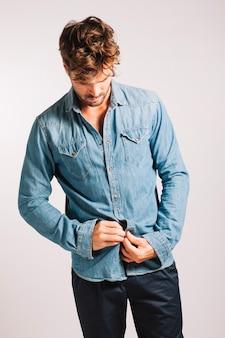 Handsome man buttoning shirt