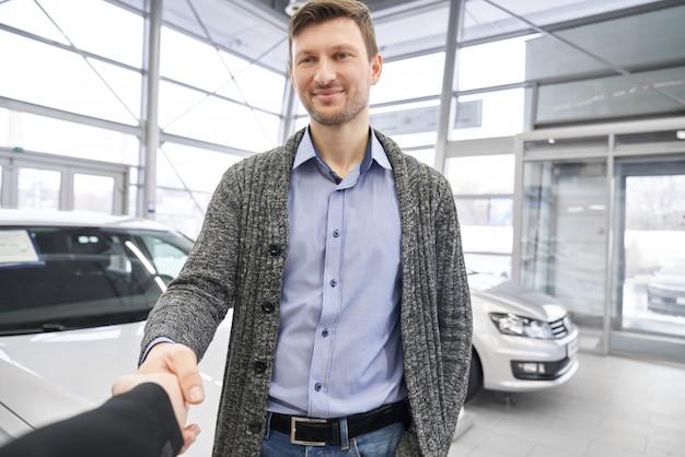 Handsome man, buyer of auto shaking hands with dealer.