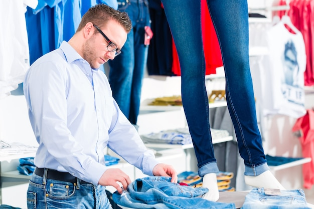 Красивый мужчина покупает синие джинсы в модном магазине или магазине