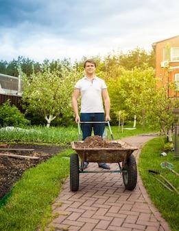 아름 다운 정원에서 수레를 들고 잘 생긴 남자