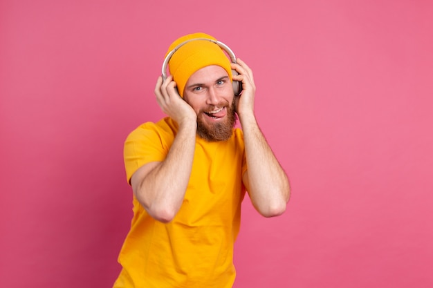 Handsome man in casual dancing with headphones isolated on pink background
