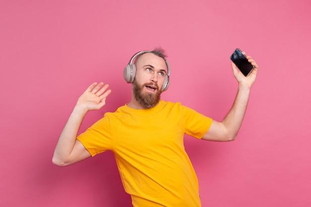 Uomo bello in balli informali con il telefono cellulare e le cuffie isolate su sfondo rosa