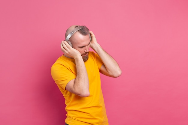 Handsome man in casual dancing with mobile phone and headphones isolated on pink background