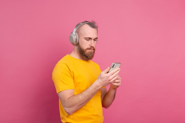 Handsome man in casual listening to music with headphones isolated on pink background