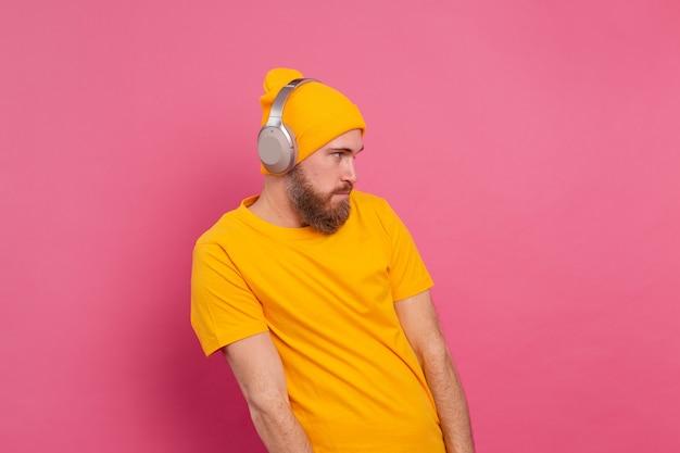 Uomo bello in ascolto casuale di musica con le cuffie isolato su sfondo rosa