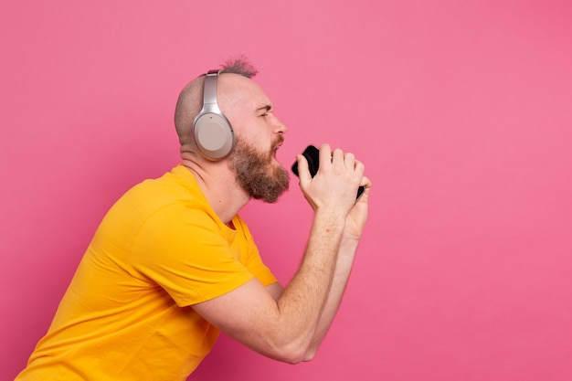 Handsome man in casual singing with mobile phone headphones isolated on pink background
