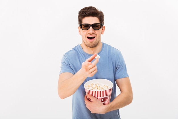 Handsome man in casual t-shirt and 3d glasses holding bucket with popcorn and pointing finger at camera, isolated over white wall