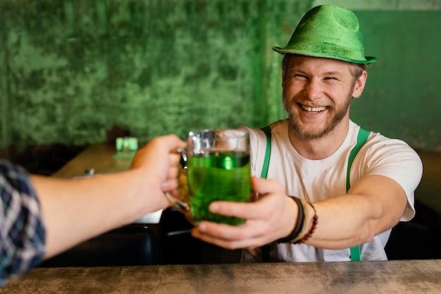 Uomo bello che celebra st. patrick's day al bar con bevande